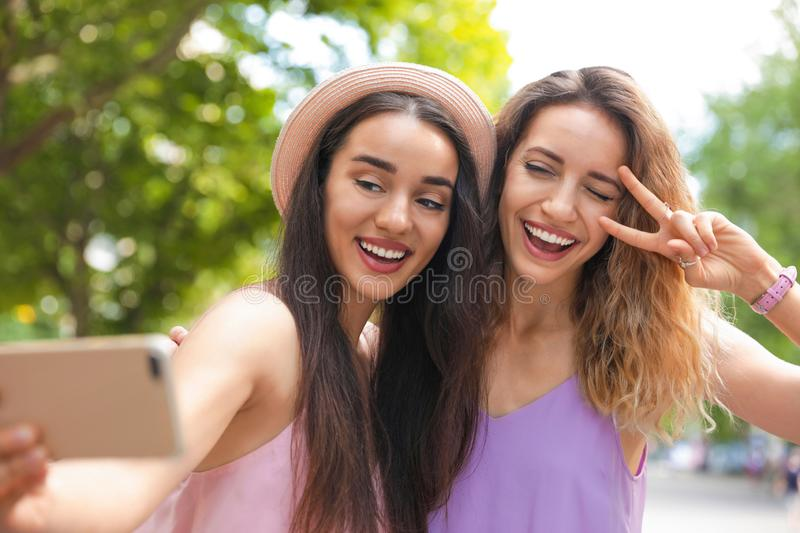 Beautiful young women taking selfie outdoors on sunny royalty free stock image