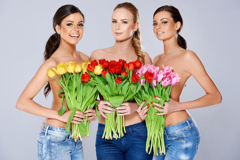 Beautiful young women with tulips. A trio of beautiful young women holding bouquets of fresh spring tulips in front of their chests as they smile at the camera royalty free stock photo