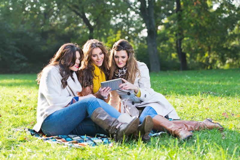 Beautiful young women using cell phones. Beautiful young women in the park using cell phones stock photos