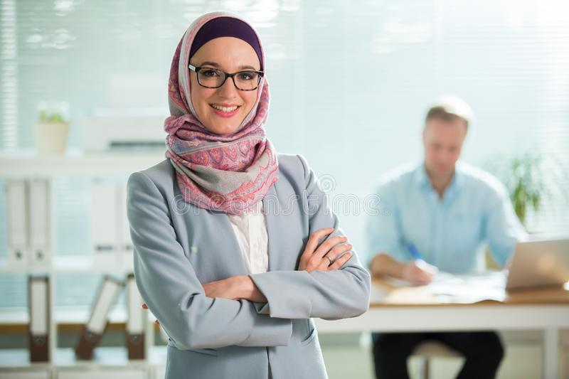 Beautiful young working woman in hijab and eyeglasses smiling in office royalty free stock photography