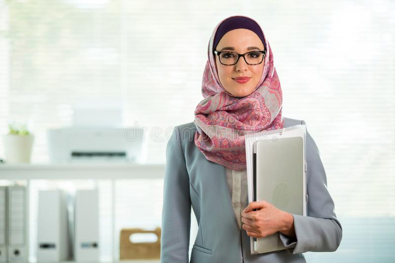 Beautiful young working woman in hijab and eyeglasses smiling in office stock photography