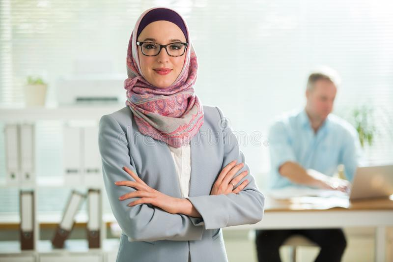 Beautiful young working woman in hijab and eyeglasses smiling in office royalty free stock photos