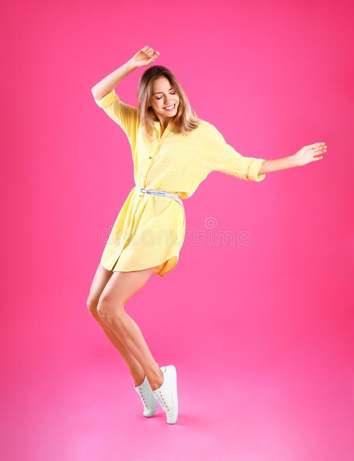 Beautiful young  in yellow dress dancing on pink background royalty free stock images