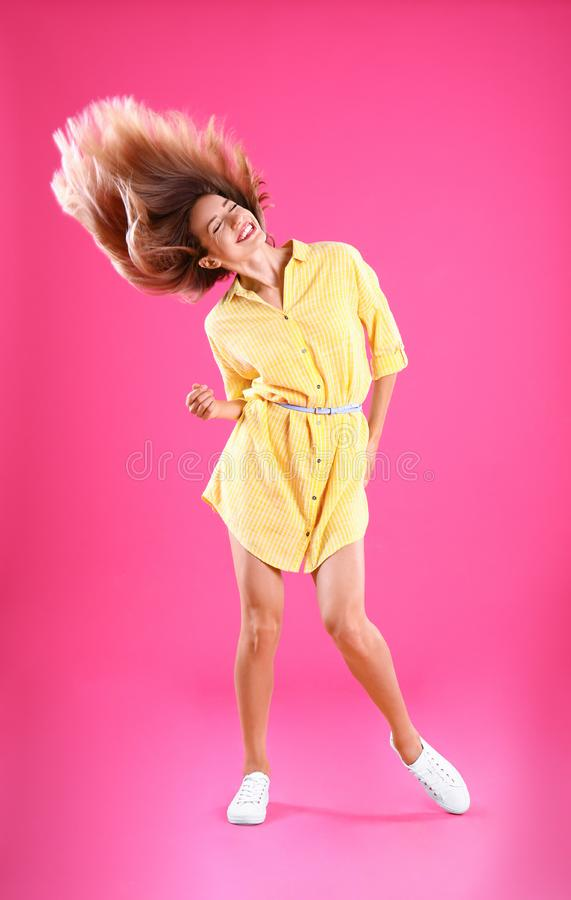 Beautiful young  in yellow dress dancing on pink background stock photography