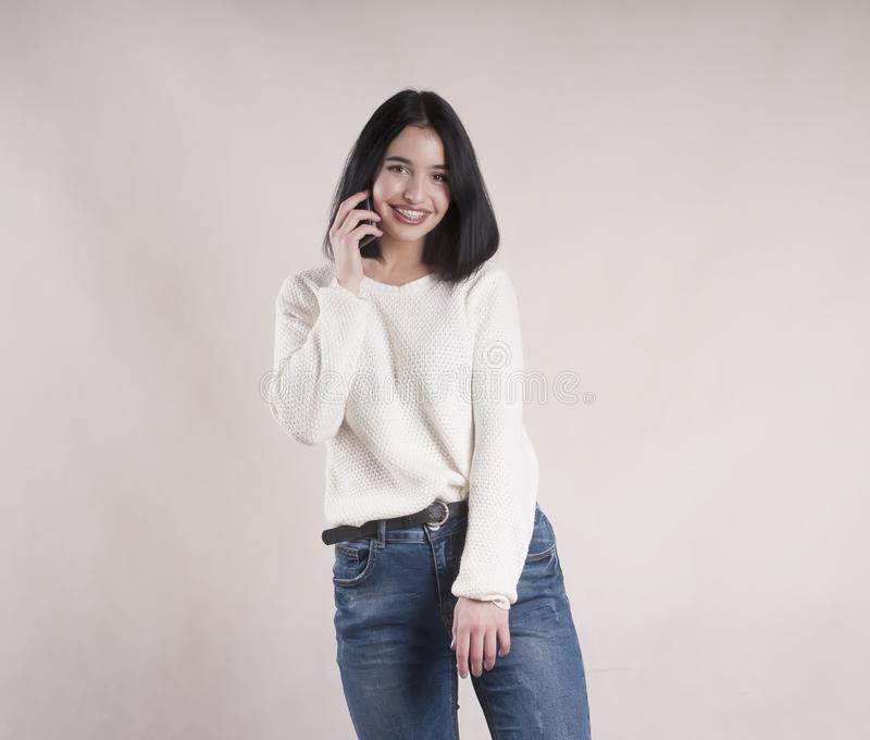 Beautiful brunette girl young wearing jeans sweater with phone studio royalty free stock photo