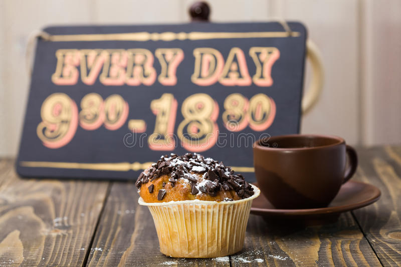 Beautiful yummy fresh muffin. And brown cup of coffee on saucer in background of retro wooden sign board with completion schedule of cafe break time indoor stock image