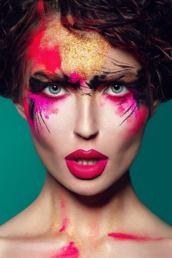Beautifulgirl med idérik färgrik makeup på en gräsplan arkivfoton