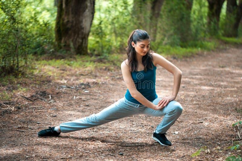 Beautifull体育女孩在公园参与健身,温暖u 库存照片