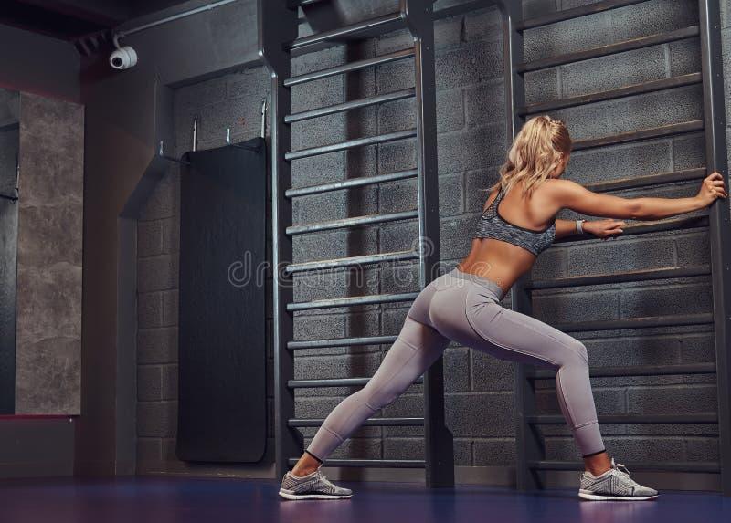 Beautifull健身妇女在现代健身中心做舒展倾斜在肋木 库存照片