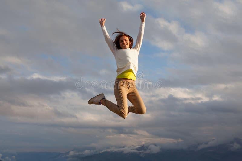 年轻beautifull女孩oa mountait跳跃的峰顶 免版税库存照片