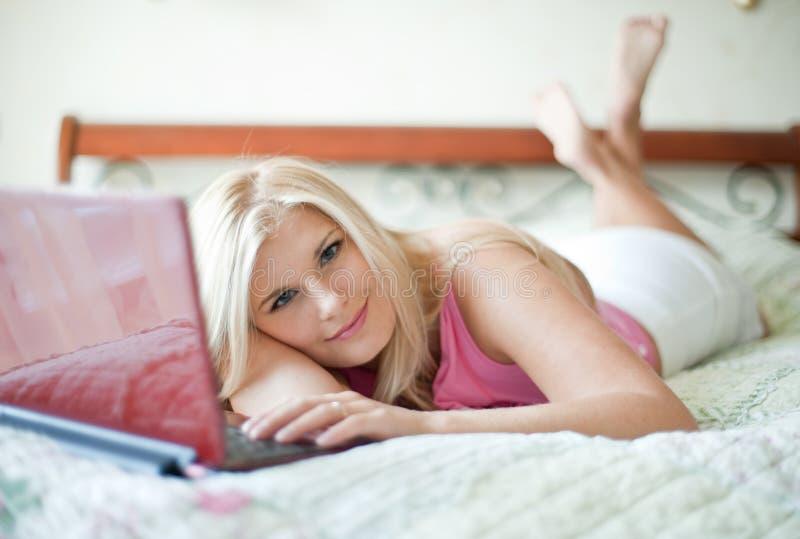 beautifull bed henne bärbar datorkvinnabarn arkivbilder