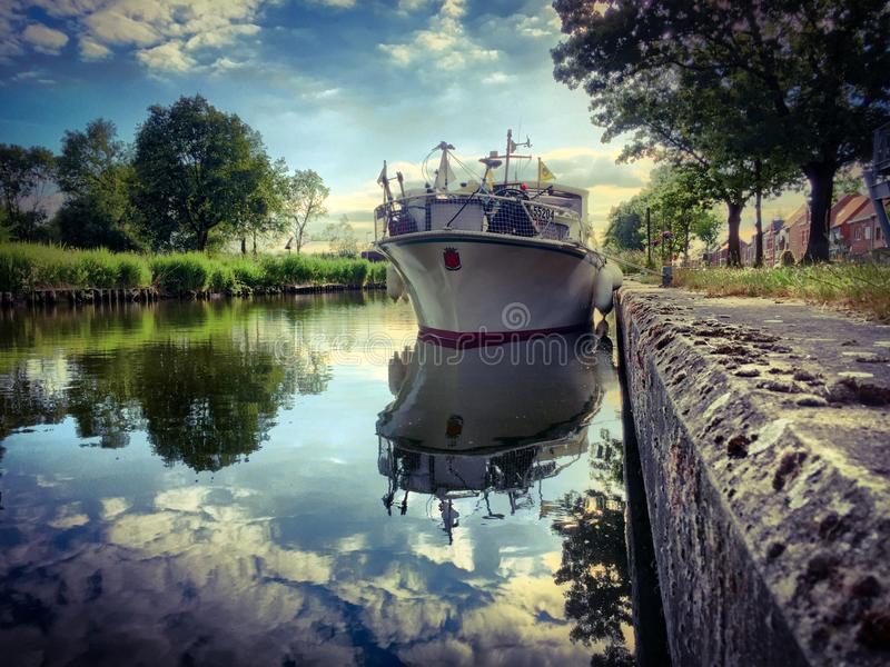 Beautifull sunset. Beautiful sunset over a canal where a yacht is stationed, and the reflection is showing in the water royalty free stock photography