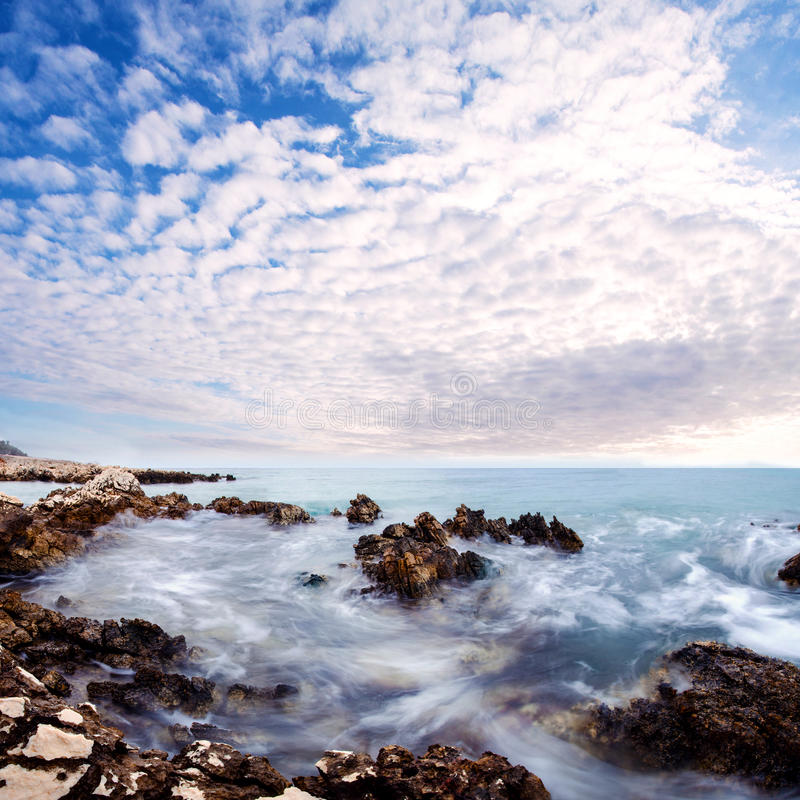 Beautifull Sunset clouds over sea stones near to beach. Sunset clouds over sea stones near to beach royalty free stock photos