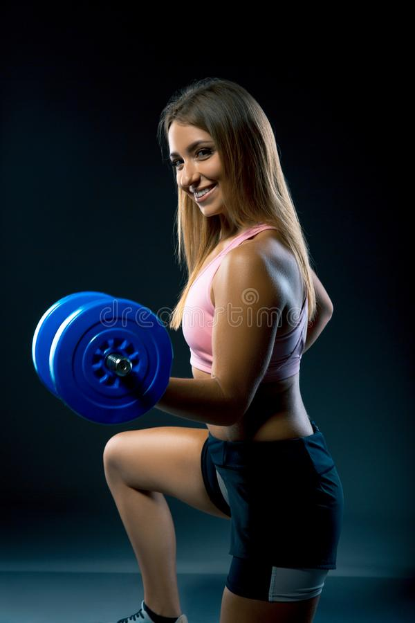 A woman with a smile on her face working out with weights, while on her knees. athlete with dumbbells trains on a dark background stock photography