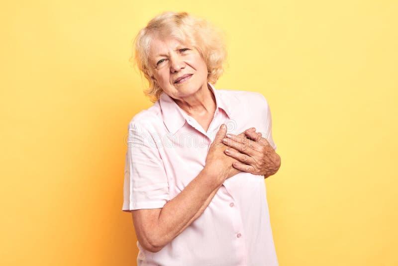 Beautifullady viejo cabelludo gris en la camisa blanca sufre de dolor del corazón imagen de archivo