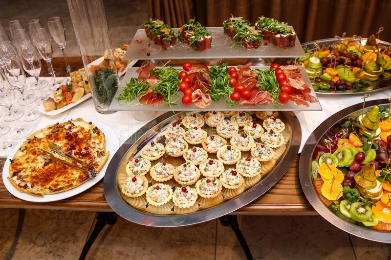 Beautifully decorated catering banquet table with different food snacks and appetizers on corporate. Christmas, birthday, party, event or wedding celebration royalty free stock image