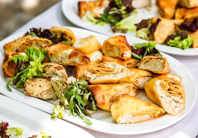 Beautifully decorated catering banquet table with different food snacks and appetizers with sandwich, pancakes, fresh salad on cor royalty free stock image