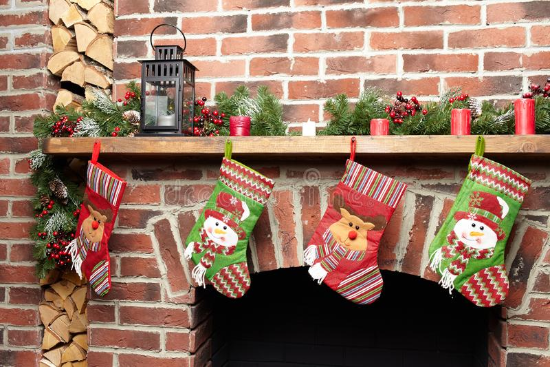 Beautifully decorated Santa Christmas socks hanging on a fireplace in brick wall waiting for presents, close-up view stock photography