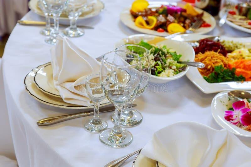Beautifully dekorerad tabelluppsättning med blommor, stearinljus, plattor och servetter för att gifta sig eller en annan händelse royaltyfri fotografi