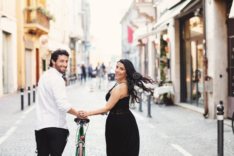 Beautifully dressed man and woman are walking in the old city with a bicycle. Love story in Rimini, Italy. Back view royalty free stock images