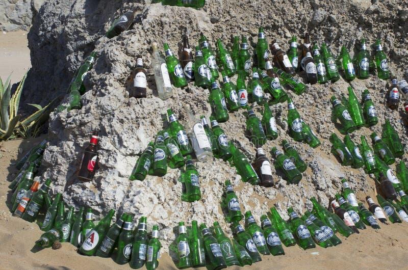 Beautifully lade ut tomma ölflaskor på en enorm stenblock i ett soligt väder arkivbild
