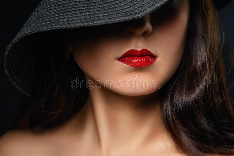 Beautifully painted red lips on the girl`s face. Model in a black hat stock image