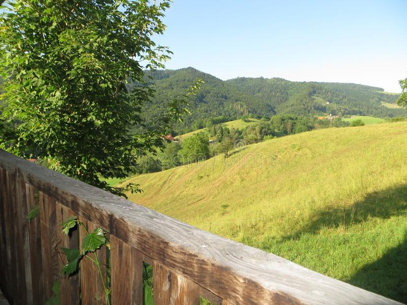 Beautifully panorama view with a turquoise blue sky, green mountains, vineyards and a wooden house balcony stock photo