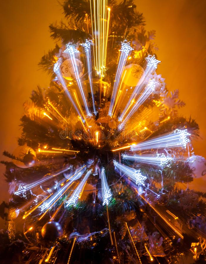 Beautifully romantic decorated Christmas tree on warm background with zoom out lights royalty free stock photography