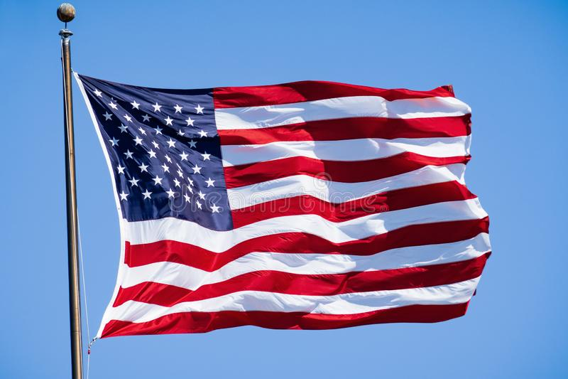 Beautifully waving star and striped American flag a blue sky background; Close Up for Memorial Day or 4th of July stock image