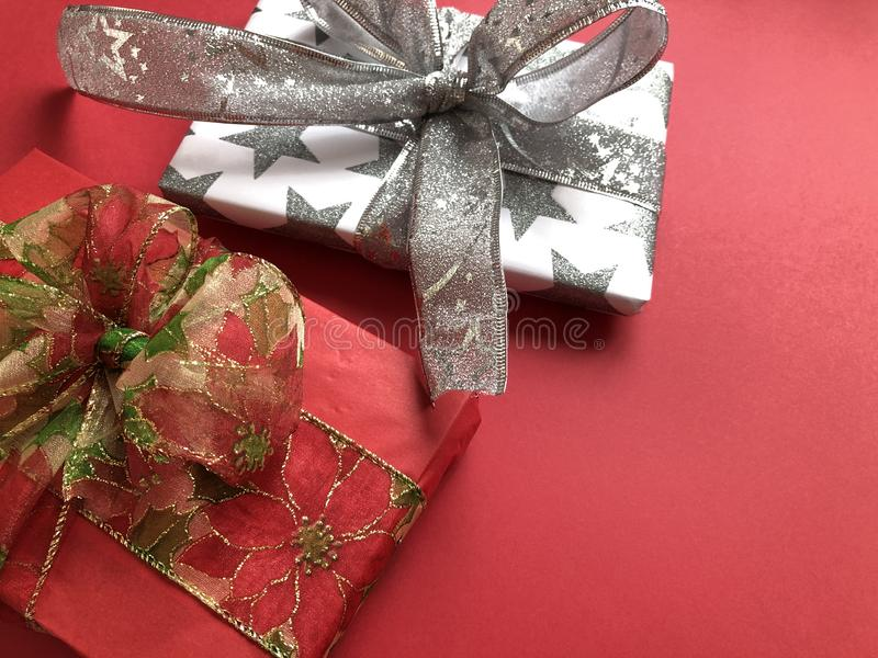 Two luxury wrapped Christmas gifts on a red background. Beautifully wrapped Christmas presents decorated with fabric ribbons tied in flamboyant bows isolated on royalty free stock photos
