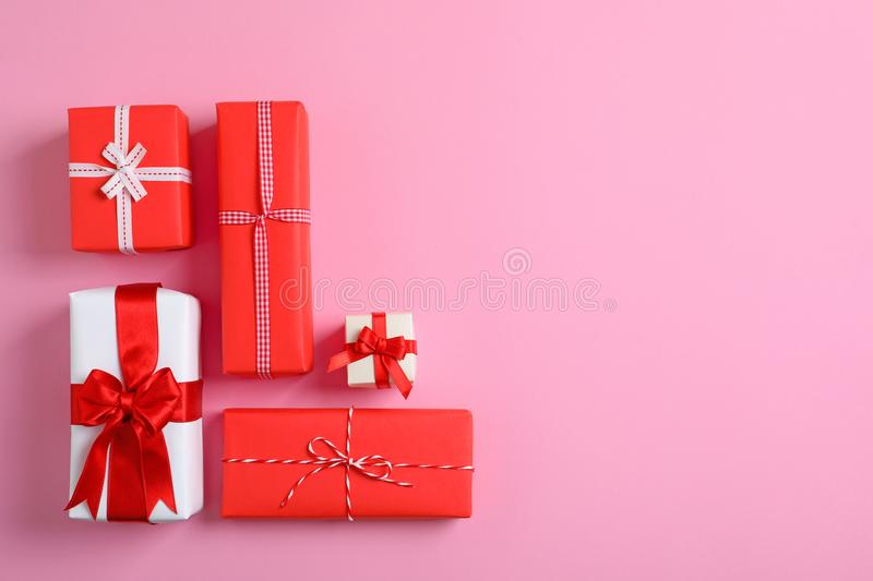 Beautifully wrapped gift boxes on color background stock photo