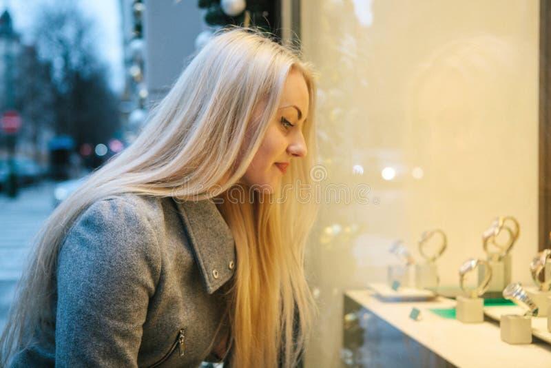 Beautifulwoman à côté d'une fenêtre de boutique pendant les vacances de Noël photos libres de droits