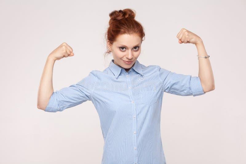 Beautifulwomanposin kijkt als bodybuilder, die bicepsen, loo tonen stock afbeeldingen