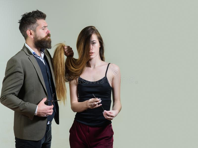 Beautify your hair today. Bearded hipster holding long hair of pretty woman and hair cutters. Professional hairdresser. Beautify your hair today. Bearded hipster stock photography