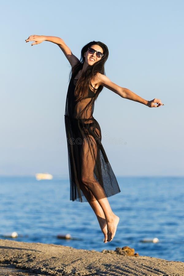 Beautifylvrouw die hoog dichtbij een oceaan springen royalty-vrije stock fotografie