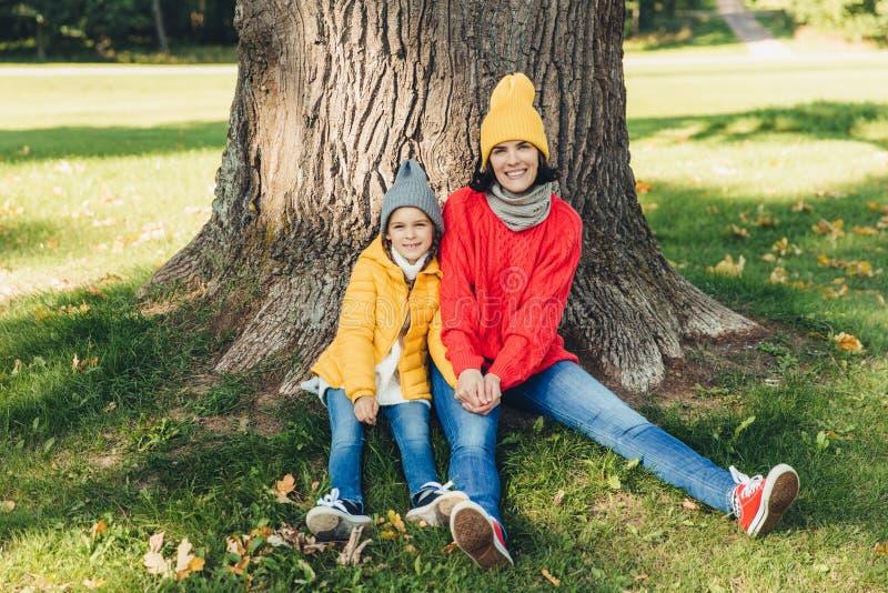 Beautiul女性戴被编织的帽子,并且swetaer与她的小女儿一起坐在树附近,有休息户外在美好的pa 库存图片