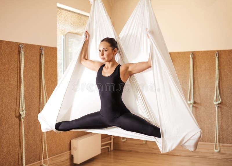 Beautiul inspiró a la muchacha que hacía yoga aérea en la hamaca blanca en el estudio fotos de archivo