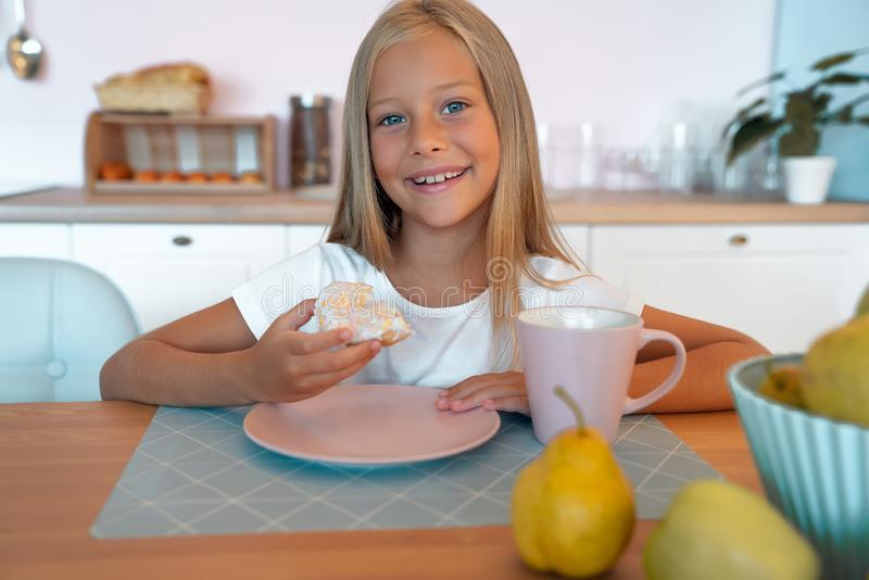 Beautuful little girl in the kitchen is having her donut with cup of tea. Looking at the camera and smiling, enjoying breakfast royalty free stock image