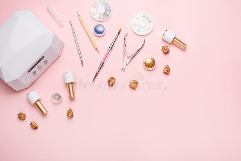 Beauty accessories for manicure and pedicure on a pink background,. Samples of nail polish, scissors, manicure ultraviolet machine. Nippers and other royalty free stock images