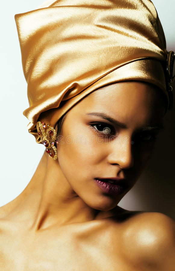 Beauty african woman in shawl on head, very elegant look with gold jewelry close up mulatto dark afro stock image