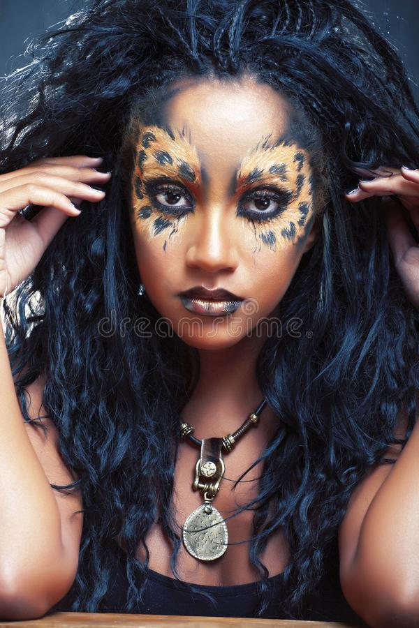 Beauty afro girl with cat make up, creative leopard print closeup, fashion style halloween look royalty free stock image