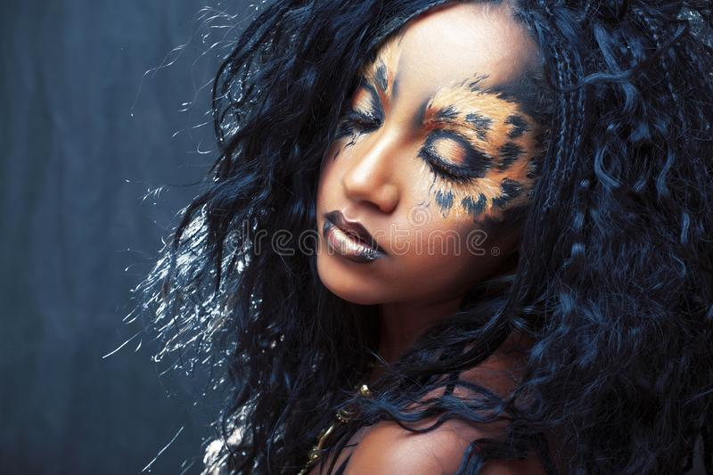 Beauty afro girl with cat make up, creative leopard print closeup, fashion style halloween look stock photos