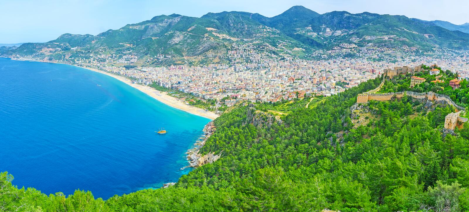 The beauty of Alanya resort. The slope of Alanya peninsula is covered with coniferous forest and neighboring with Kleopatra beach, that is seen from the Castle royalty free stock photos