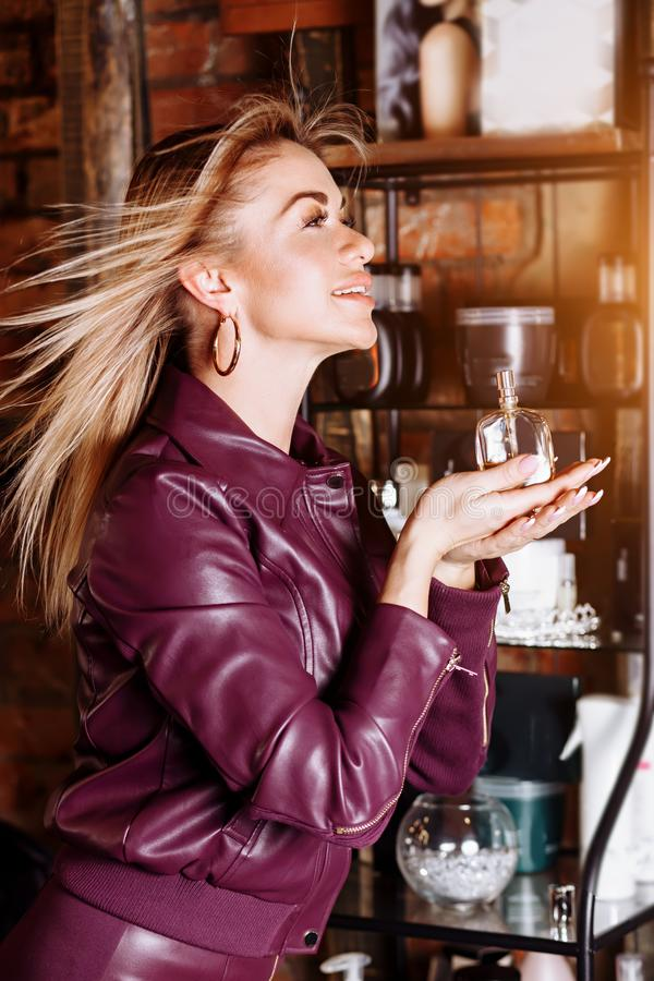 Beauty, aroma, people and body care concept. Young attractive woman with blond flying hair wearing violet leather jacket holding royalty free stock photos