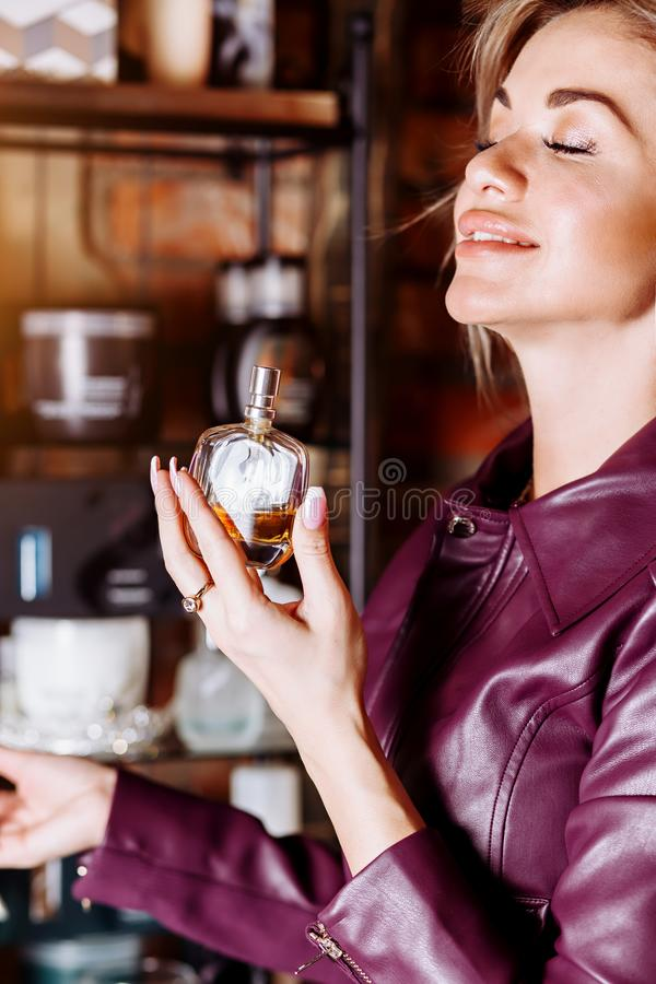 Beauty, aroma, people and body care concept. Young attractive woman with blond flying hair wearing violet leather jacket holding stock photos
