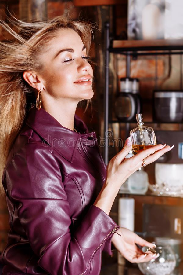 Beauty, aroma, people and body care concept. Young attractive woman with blond flying hair wearing violet leather jacket holding stock images