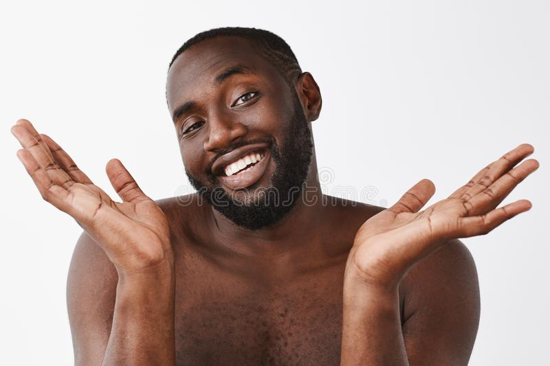 Beauty as it is. Joyful self-assured and funny dark-skinned man with beard, posing naked over gray background, smiling. Broadly with carefree smile and royalty free stock image