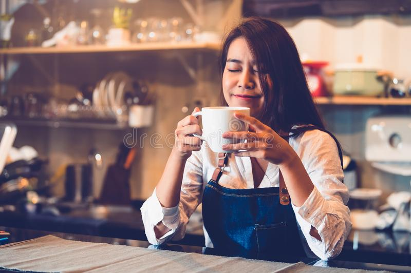 Beauty Asian female barista holding cup of coffee and tasting brewed coffee  with cafe restaurant background. Waitress smelling. Coffee at cafeteria. Food and royalty free stock photos
