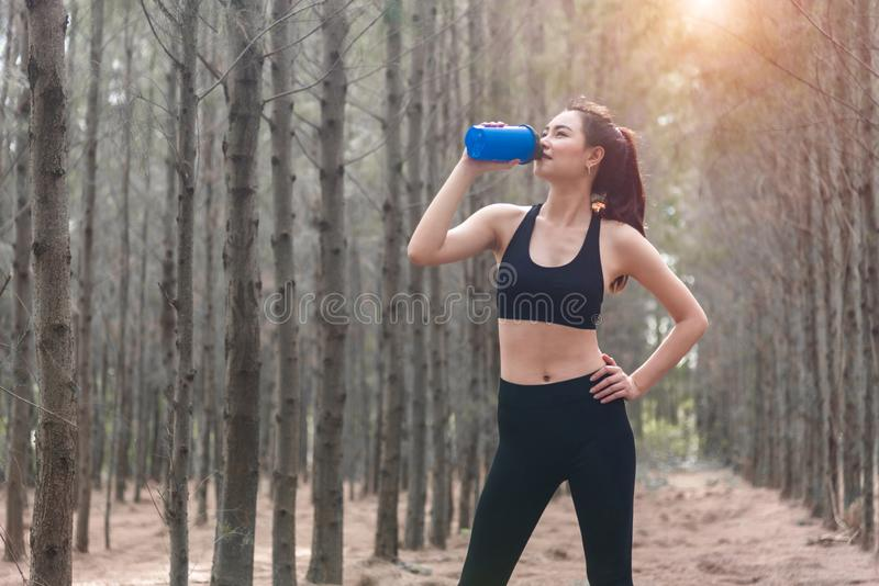 Beauty Asian sport woman resting and holding drinking water bottle and relaxing in middle of forest after tired from jogging. Girl looking attraction view royalty free stock images