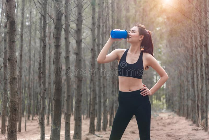 Beauty Asian sport woman resting and holding drinking water bottle and relaxing in middle of forest after tired from jogging. Girl. Looking attraction view stock photography